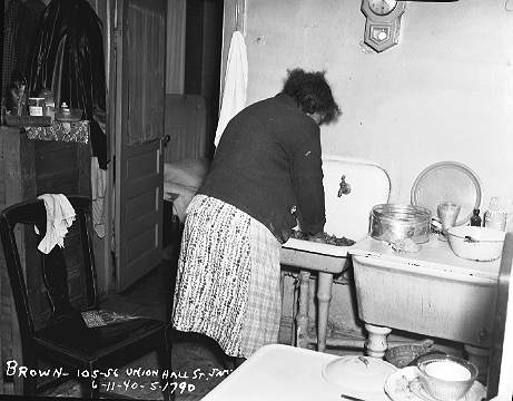 Mrs. Brown washing up in the kitchen of her apartment at 105-56 Union Hall Street, Jamaica, Queens, June 11, 1940. In the early years, the Housing Authority frequently photographed prospective residents for new projects as part of the selection process. ID# 02.002.01790