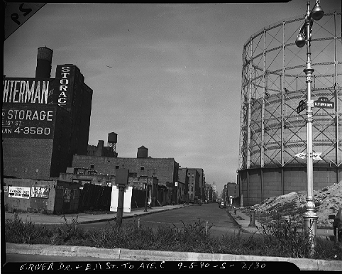 East 11th Street looking west toward Avenue D from the East River Drive on the Lower East Side (East Village), September 5, 1940. These buildings, as well as the tank containing manufactured gas (a dozen of them gave the area from East 11th to East 20th Streets the monicker Gas House District) were bulldozed for the 18 acre Jacob Riis Houses.  ID# 02.002.02130