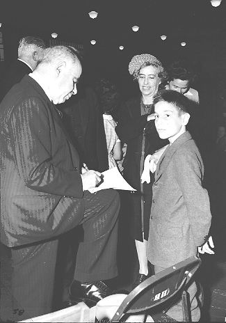 New York State Governor Herbert Lehman signing his autograph for a young resident of Fort Greene Houses, September 9, 1942.  ID# 02.003.01260