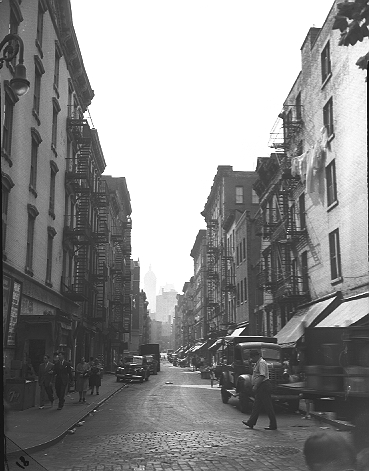 Oak Street, looking west from Catherine Street, on the Lower East Side of Manhattan, September 7, 1944. These tenements were demolished, and Oak Street disappeared, in the 22-acre clearance for the construction of Smith Houses. In the distance is the 1908 Singer Building, demolished in 1968. 