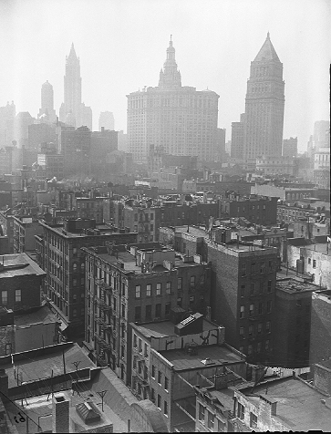 Tenements along Oak Street at Catherine Street looking northwest toward the Municipal Building (center) and the U.S. Courthouse on Foley Square (right), April 7, 1944. The Woolworth Building and Ernest Flagg's Singer Building (demolished in 1968) are at left. The tenements were cleared (and Oak Street disappeared) to build Smith Houses, completed in 1953.  ID# 02.003.05172
