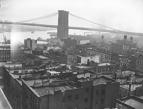 The roofs of a variety of 1879-1901 Old Law tenements (dumbbell-shaped airshaft, foreground), New Law (post-1901), and pre-Old Law tenements are in this view shot from Oak Street and Catherine Street looking southeast toward the Brooklyn Bridge, September 7, 1944. This entire area was part of 22 acres cleared away to build Smith Houses.  ID# 02.003.05174