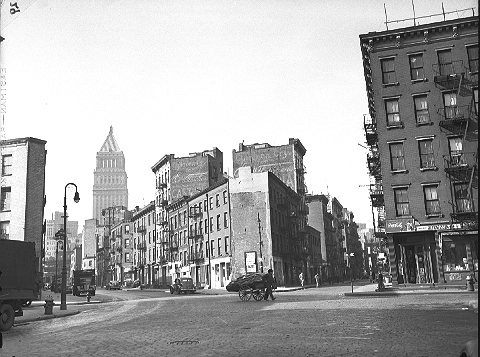 New Chambers Street, looking north from James Slip, March 13, 1945. These buildings (and streets) disappeared (and so, presumably, did the pushcarts) in the clearance for the Gov. Alfred E. Smith Houses. The tall building in the distance is the Cass Gilbert-designed U.S. Courthouse (1936) in Foley Square.  ID# 02.003.05474