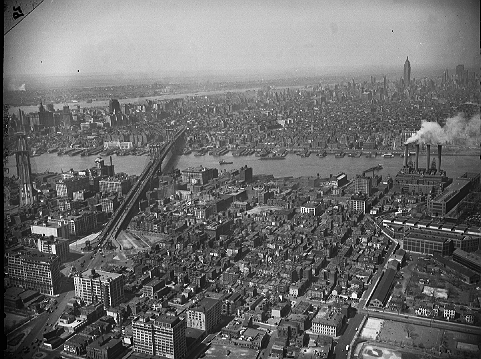 Aerial shot of Brooklyn between the Manhattan Bridge and the Brooklyn Navy Yard (which begins at the right edge of the picture), April 19, 1946. Some 17 acres in the foreground would be cleared for the building of the 1952 Farragut Houses.  ID# 02.003.06102