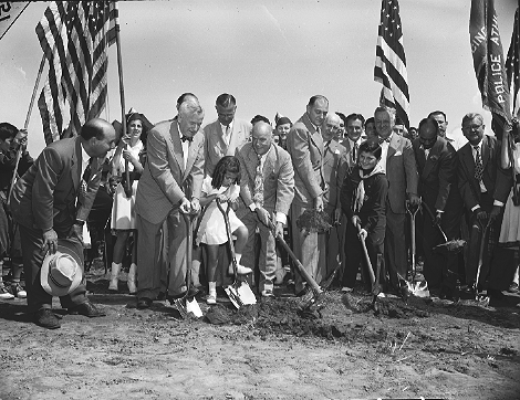 A real occasion -- General Thomas Farrell, chairman of NYCHA (in bowtie), is the chief spade wielder for ground breaking of South Beach Houses on Staten Island, August 18, 1948. ID# 02.003.08798