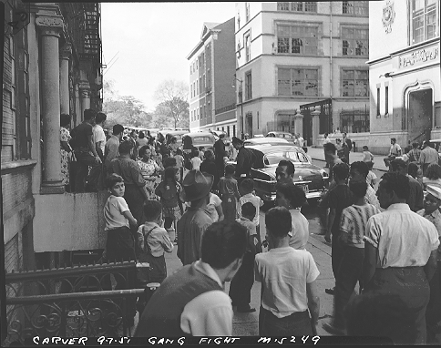 "The NYCHA photographer labeled this September 7, 1951 photo ""Carver gang fight."" However, it looks like a street disturbance in East Harlem outside a public school (right), which a couple of uniformed police officers are investigating, drawing a crowd.  ID# 02.003.15249"