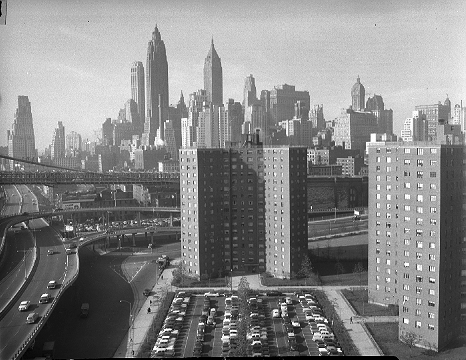 Smith Houses in the foreground is dwarfed by the lower Manhattan skyline, November 11, 1956. The three center skyscrapers are, from left, the Farmers Trust, now 20 Exchange Place (1931), 791 feet; Cities Service a/k/a 60 Wall Tower, now called American International (1932), 952 feet; and the Bank of the Manhattan Company a/k/a 40 Wall Street, now the Trump Building (1930), 927 feet. The bell-shaped tower of the 612-foot Singer Building (1908) is at right; it was demolished in 1968.  ID# 02.003.24673
